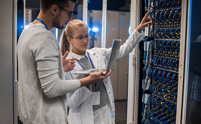 Woman and man looking at networking equipment